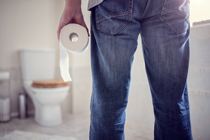 Man holding a roll of toilet paper looking at a toilet
