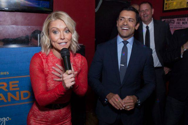 Kelly Ripa speaking into a microphone while Mark Consuelos laughs next o her.