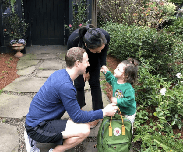 Mark Zuckerberg holding a backpack and greeting his daughter.