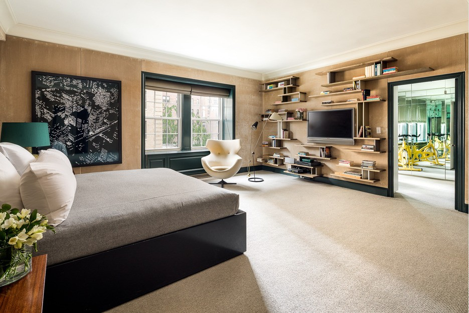Large master bedroom with tan walls and shelving
