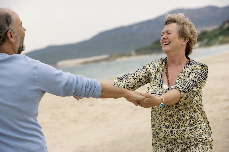 senior couple dancing on beach, smiling
