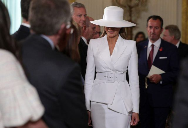 Melania Trump in her white outfit and hat.