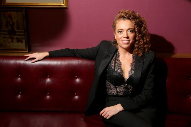 Michelle Wolf sits on a leather sofa.