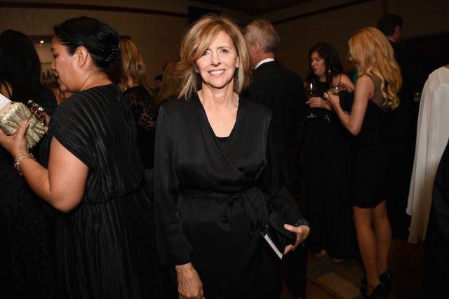 Nancy Meyers poses in a black dress at a party.