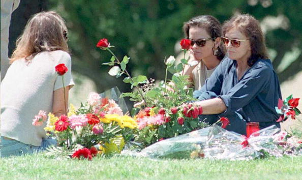 Murder victim Nicole Brown Simpson's mother Juditha (R), and sisters Denise (C) and Tanya (L) sit next to her grave surrounded by flowers.