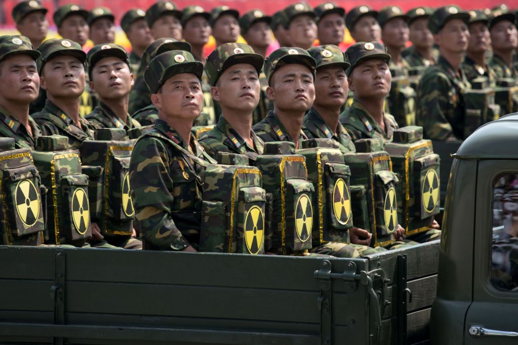 Korean People's Army (KPA) soldiers carrying packs marked with a radioactive symbol