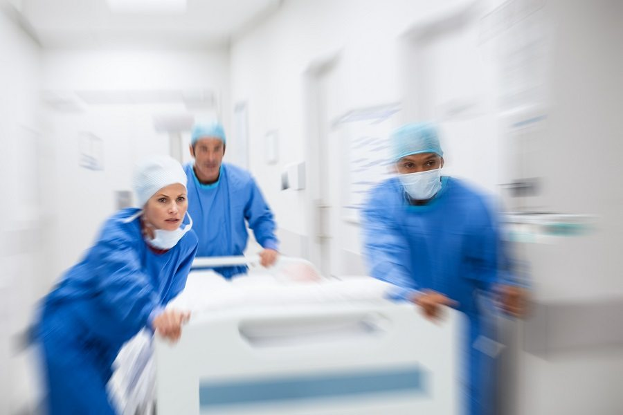Doctors rushing with Patient lying on bed