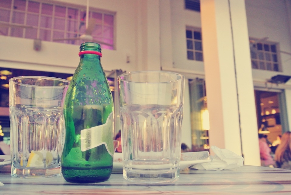seltzer waterbottle and two glasses on the table in an open air cafe or restaurant