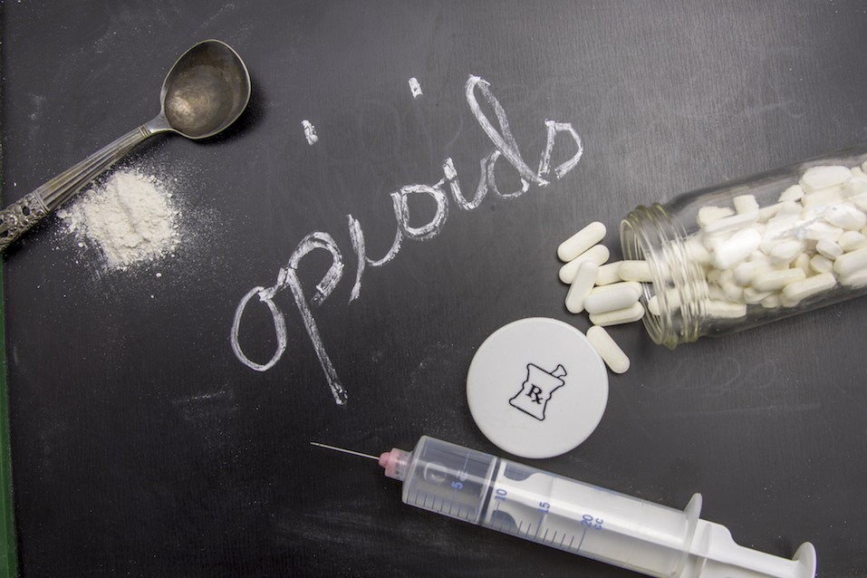 Opioids written in chalk on blackboard with crushed powder, spoon, syringe, and prescription vial.
