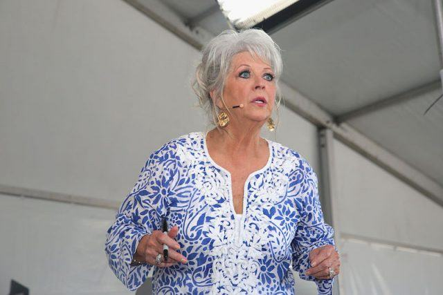 Paula Deen speaking while stage in a large tent.