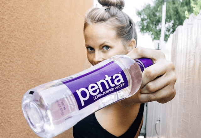 A woman holds a bottle of Penta.