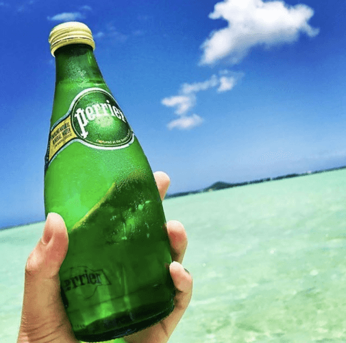 A person holds a bottle of Perrier on the beach.