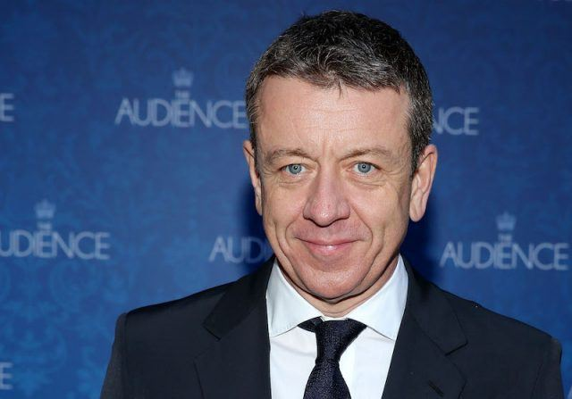 Peter Morgan stands on a red carpet wearing a black suit and tie.