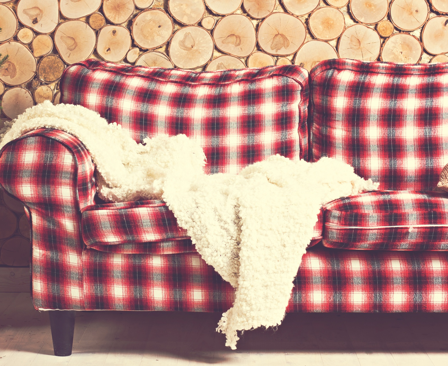 Red Plaid couch with wooden wall