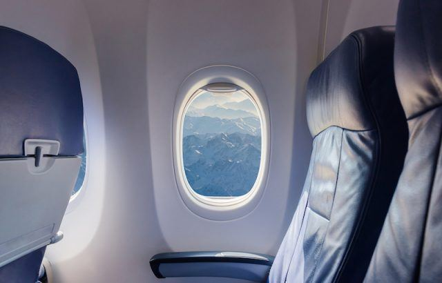 A window on a plane with the shades up.