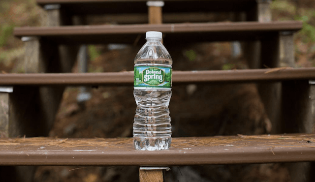 A Poland Spring water bottle on a wooden step.