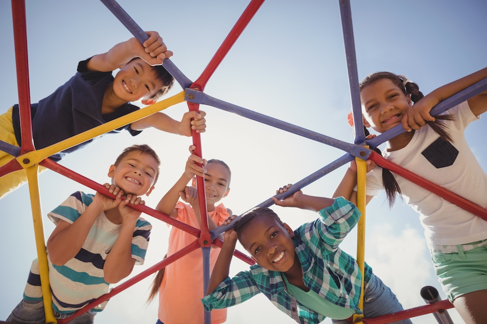 happy schoolkids looking through dome climber at school playground