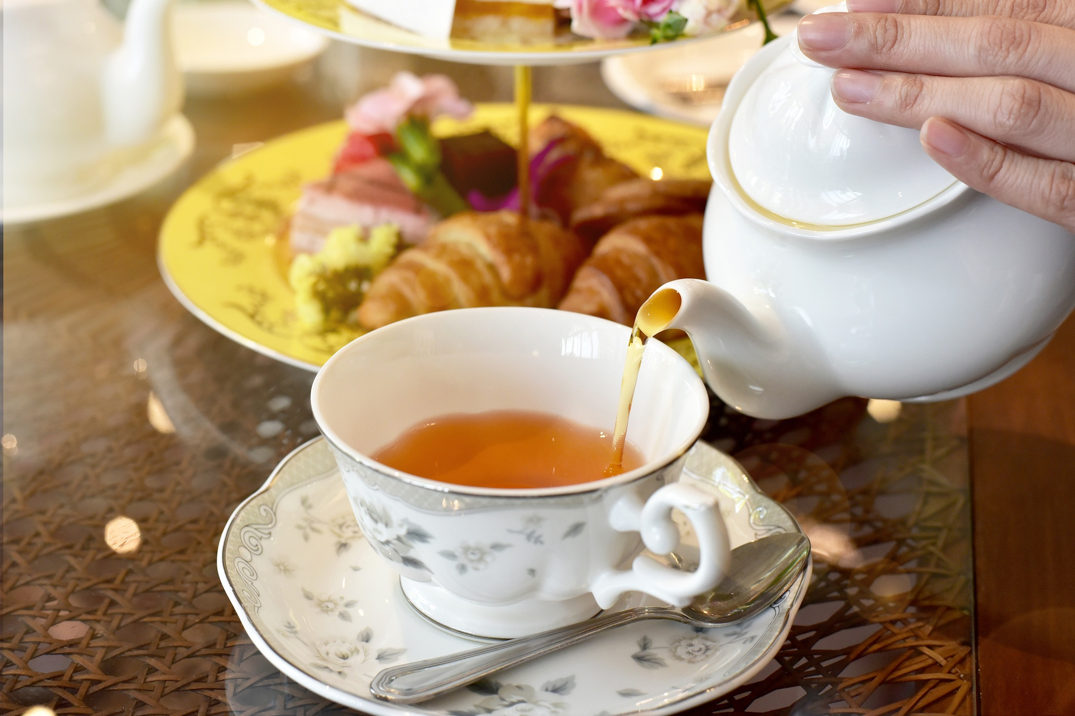 Pouring tea from vintage teapot to the cup, English Tea Time.
