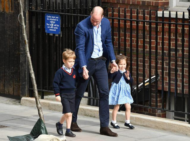 Prince William holding Prince George and Princess Charlotte's hands.