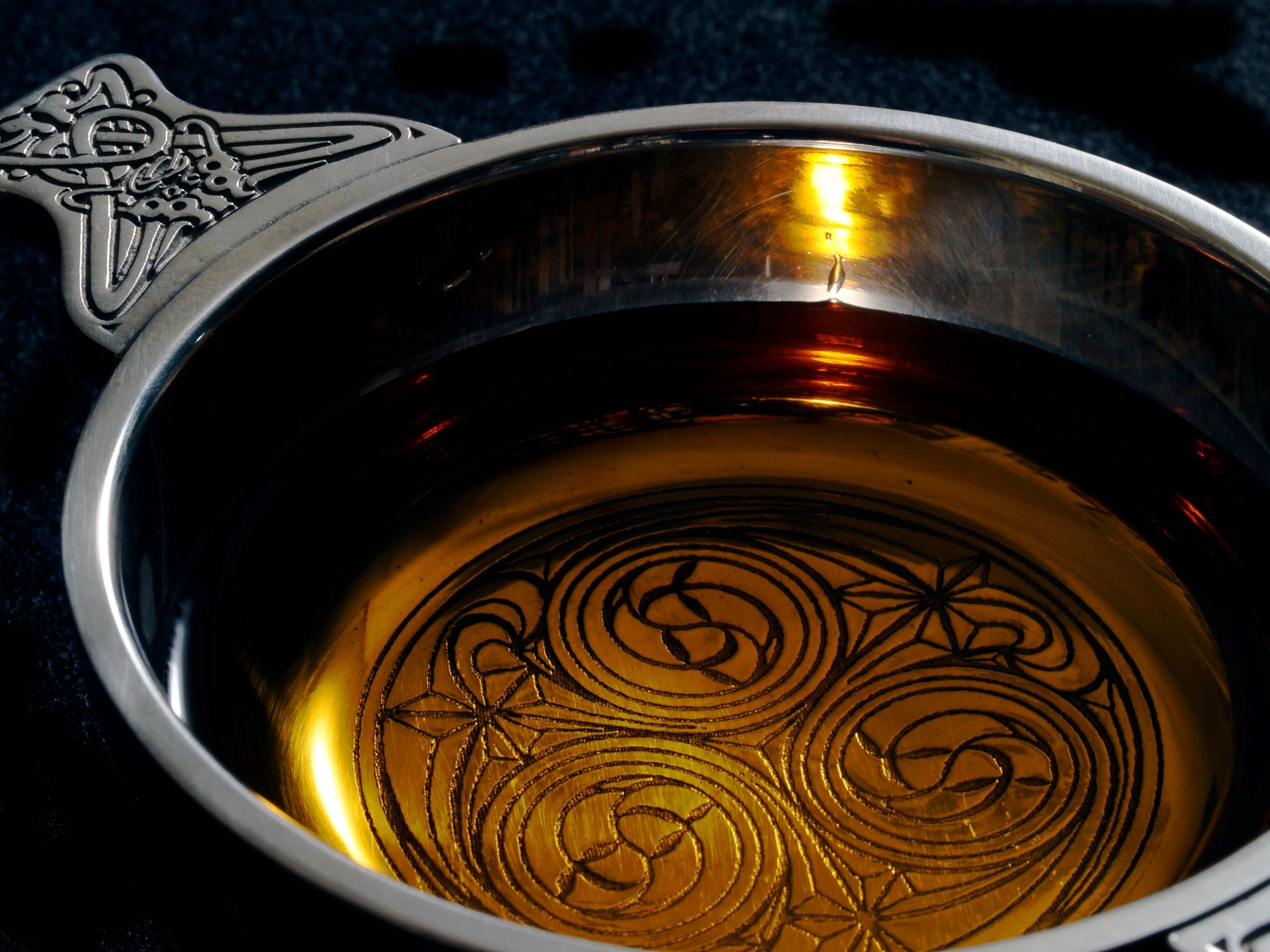 A traditional Scottish cup, a quaich, with a dram of single malt whiskey.