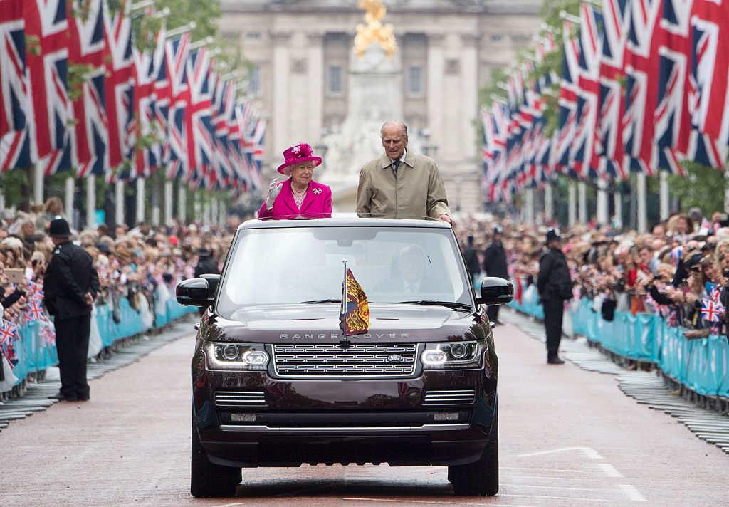 Britain's Queen Elizabeth II (C) waves as to guests as she arrives in the Royal box