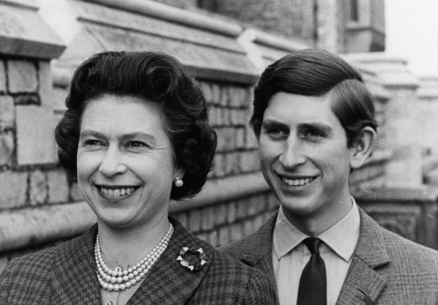 An archived photo of Queen Elizabeth and prince Charles smiling together.
