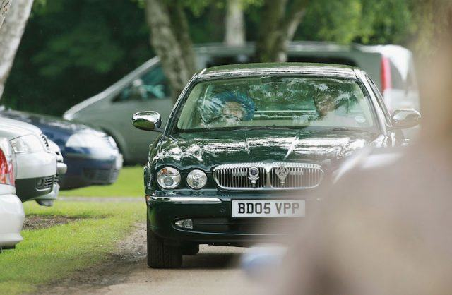Queen Elizabeth driving a black and shiny car.