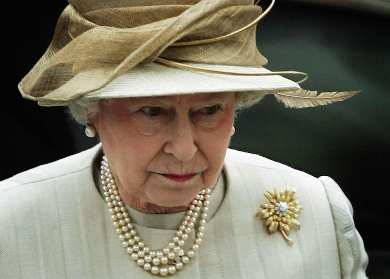Queen Elizabeth II looking serious while wearing pearls, a hat and a brooch.