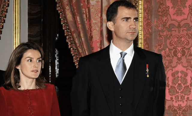 Queen Letizia stands next to Prince Felipe at a formal event.