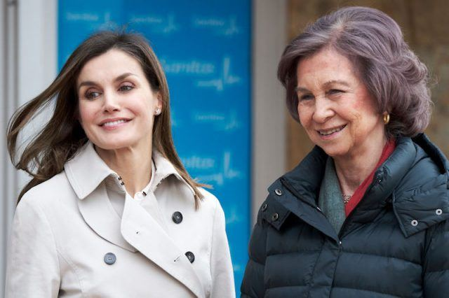 Queen Letizia stands next to Queen Sofia outside building.
