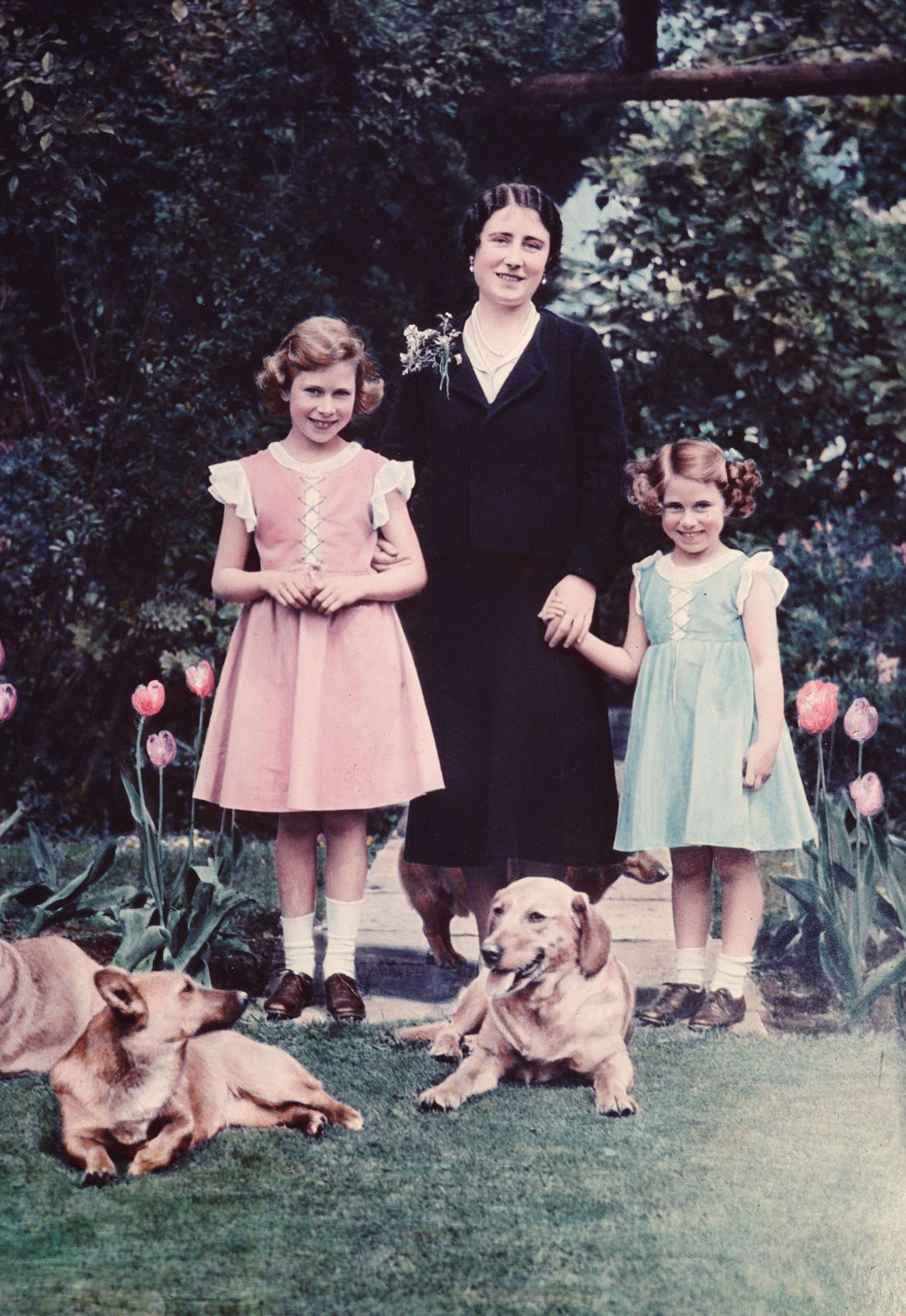 Britain's Queen Elizabeth, center, poses with her two daughters, Princess Elizabeth, left, and Princess Margaret, in June 1936 in the garden of the Royal Lodge at Windsor, England.