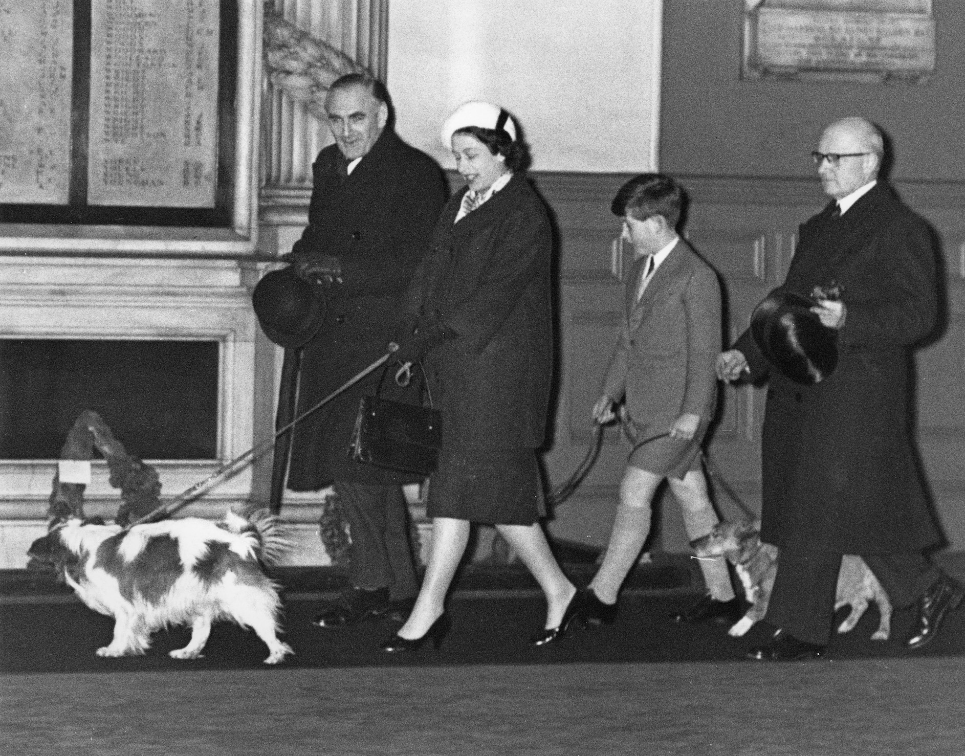 Queen Elizabeth II and Prince Charles walk through Liverpool Street Station in London with their dogs