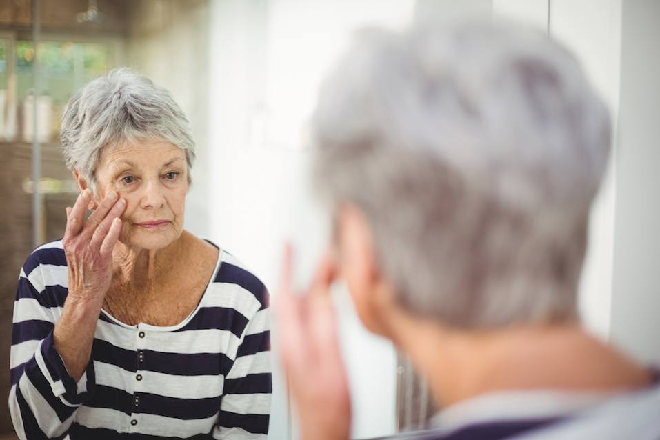 senior woman looking at skin in mirror in bathroom