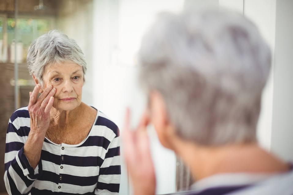 senior woman looking at skin in mirror in bathroom