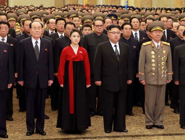 Kim Jong Un and Ri Sol Ju standing together in a room filled with military and political officials.