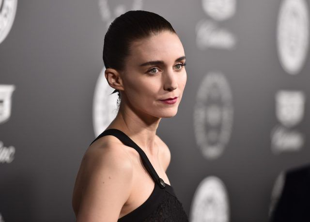 Rooney Mara poses on a red carpet in a black dress.