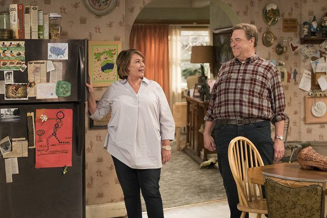 Roseanne standing in front of the fridge as she talks to Dan in the kitchen.
