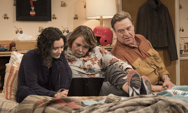 Roseanne, Darlene and Dan look at a laptop while sitting on a bed.