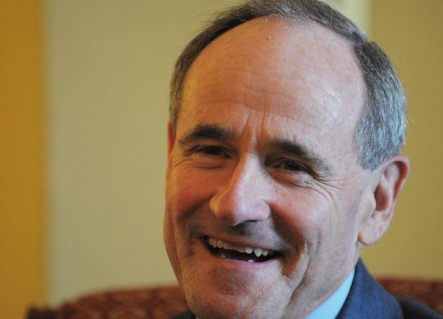 Jim Risch sits on a couch and smiles.