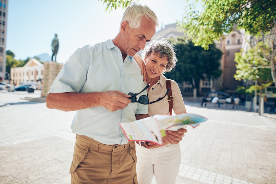senior couple standing outdoors in the city looking at a map