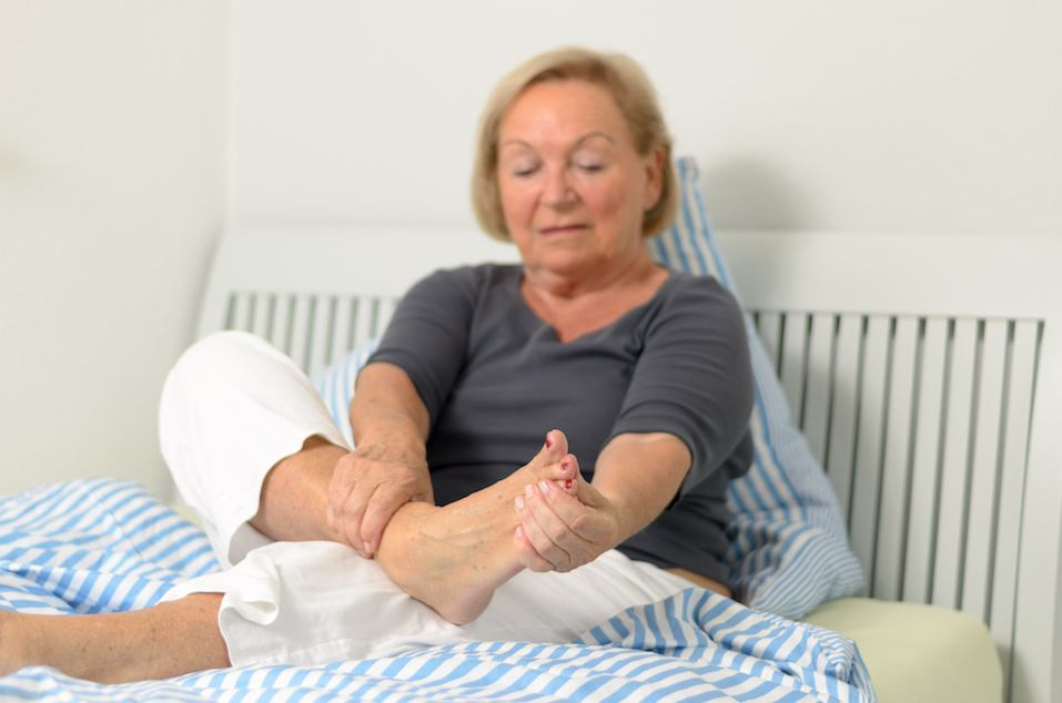Senior lady massaging her bare foot to relive aches and pains