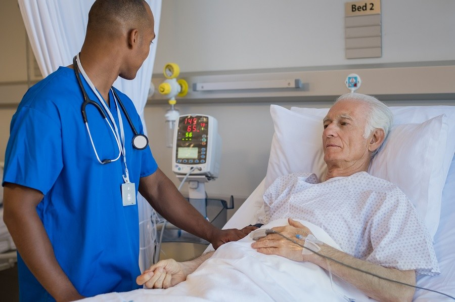 Patient lying on bed with a nurse there to help him