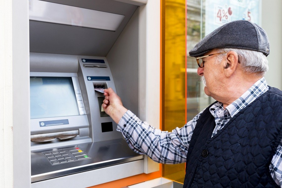 elderly man inserting credit card to ATM outdoor