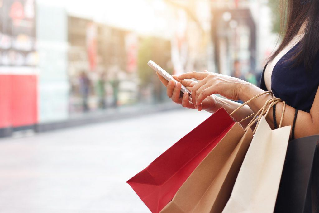 woman checking her phone with shopping bags in hand