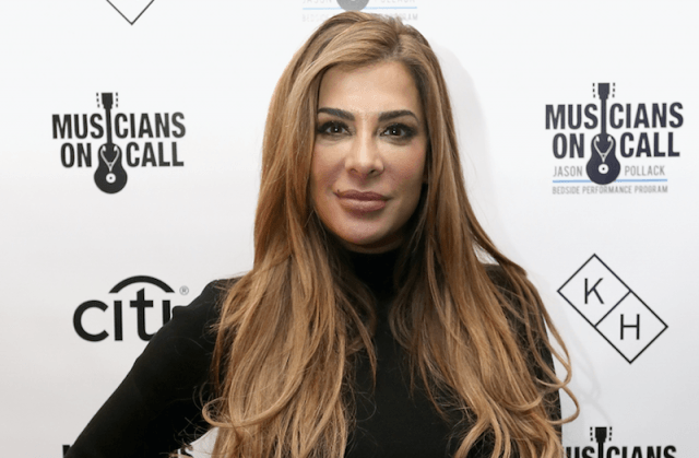 Siggy Flicker posing for photographers on a red carpet.