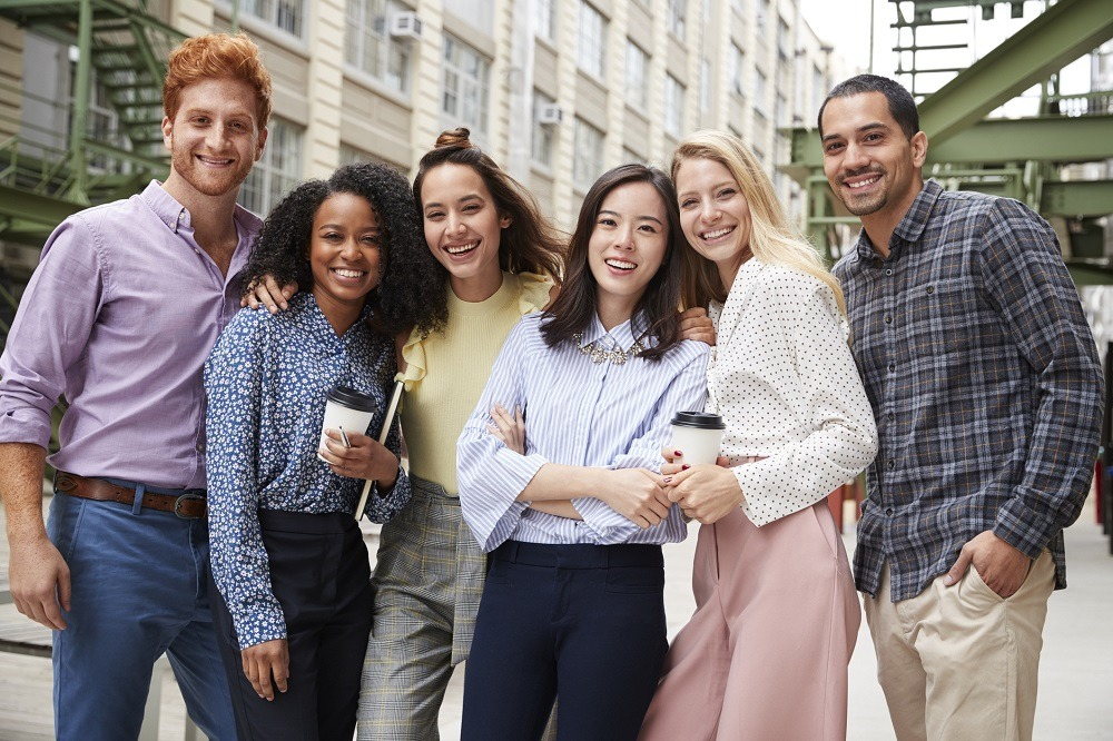 Six young adult co-workers standing together