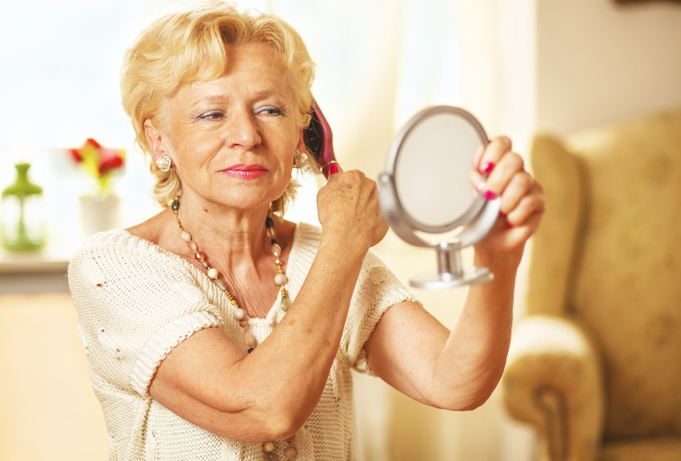 Smiling elderly woman comb hair and looked in the mirror