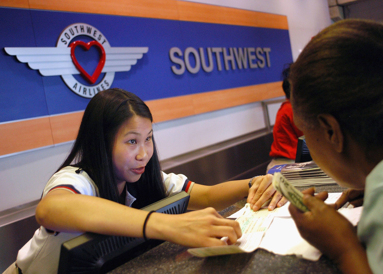 Southwest Airlines employee Agnes Chu of Oakland, California assists passenger Lois Ryals of Philadelphia, Pennsylvania at Philadelphia International Airport