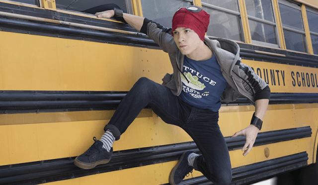 Peter on the side of a school bus wearing Spider-Man's mask.