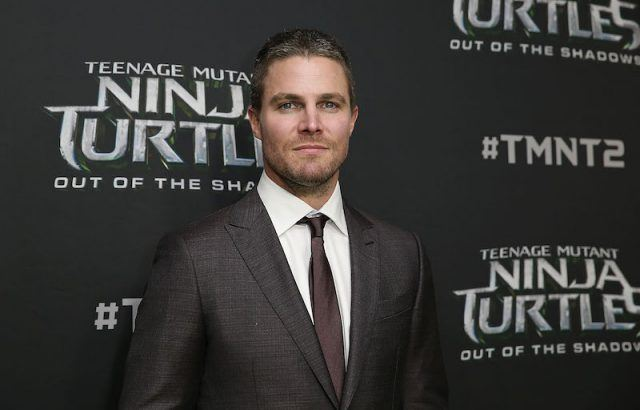 Stephen Amell in a black suit and dark tie on a red carpet.